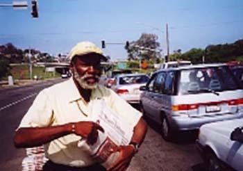 Man selling newspapers in traffic