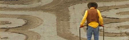 man in yellow shirt tilling dirt