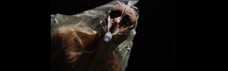 Head and torso of man covered in plastic