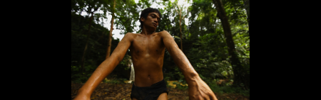 Man dancing in jungle with no shirt
